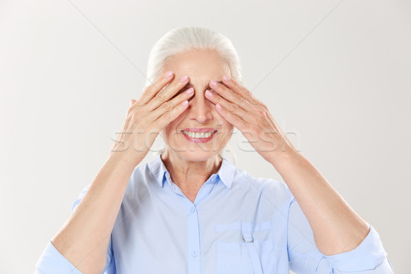 Senior grey-haired woman covering her eyes with both hands Stock photo © deandrobot