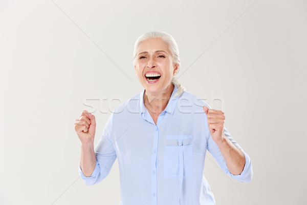 Oude vrouw vieren winnen geïsoleerd witte vrouw Stockfoto © deandrobot