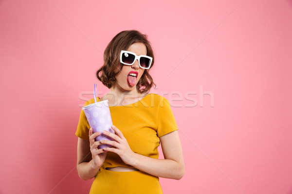 Portrait of a funnny girl in sunglasses holding cup Stock photo © deandrobot