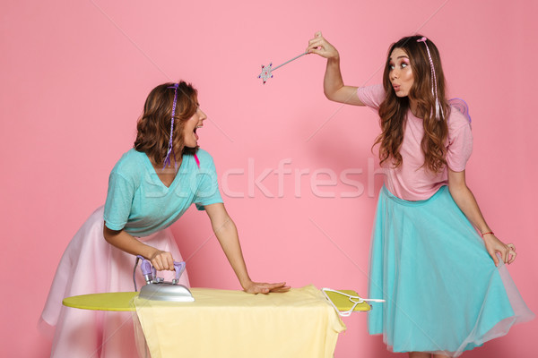 Portrait of a two cheerful young girls ironing clothes Stock photo © deandrobot
