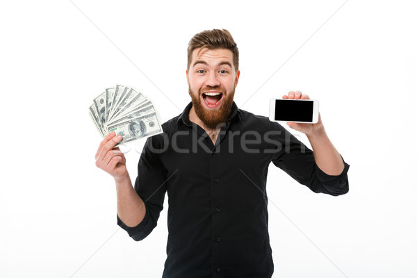 Surprised pleased bearded business man in shirt holding money Stock photo © deandrobot