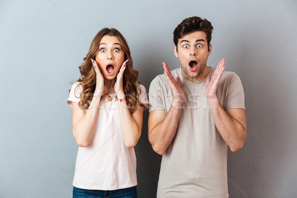 Happy excited couple standing with hands at their face Stock photo © deandrobot