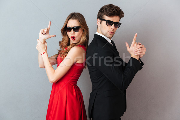 Portrait of a beautiful playful couple dressed in formal wear Stock photo © deandrobot