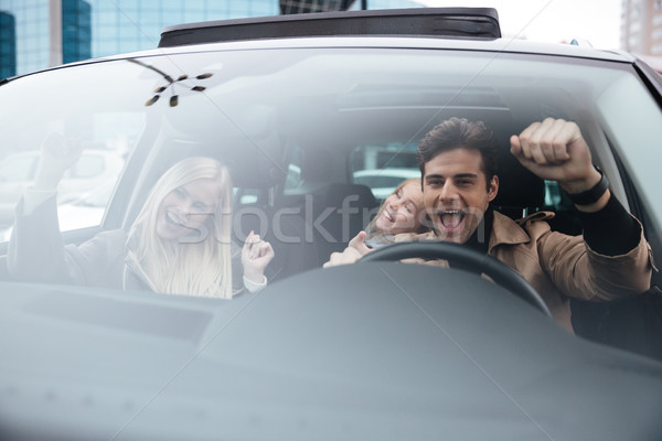 Happy emotional man sitting in car with wife and daughter Stock photo © deandrobot
