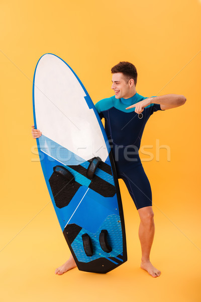 Full length photo of cheerful young man in swimsuit pointing wit Stock photo © deandrobot