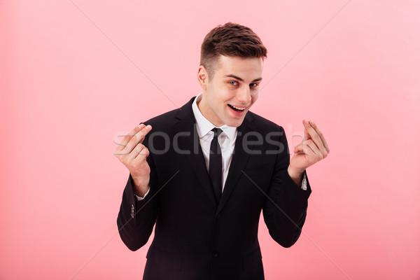 Fiatal vicces férfi mutat pénz kézmozdulat Stock fotó © deandrobot