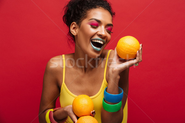 Food fashion photo of joyful mixed-race woman with colorful make Stock photo © deandrobot