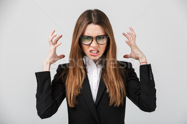 Angry businesslady frown and gesturing with hands isolaed Stock photo © deandrobot