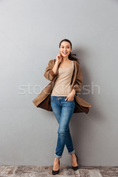 Full length of a smiling young asian woman twisting around Stock photo © deandrobot