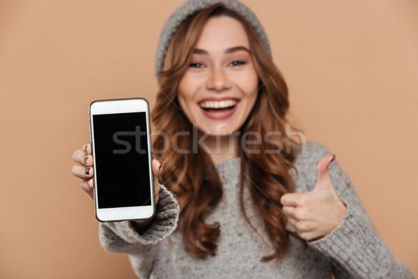 Close-up portrait of charming brunette woman in woolen hat showi Stock photo © deandrobot