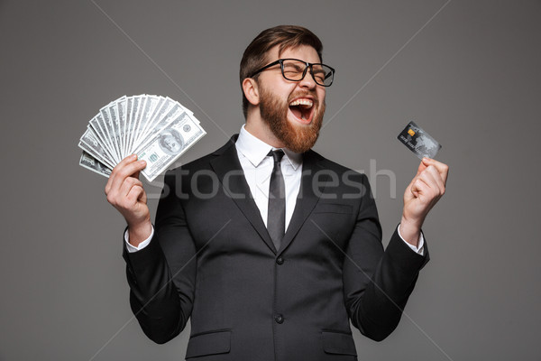 Portré elégedett fiatal üzletember tart pénz Stock fotó © deandrobot