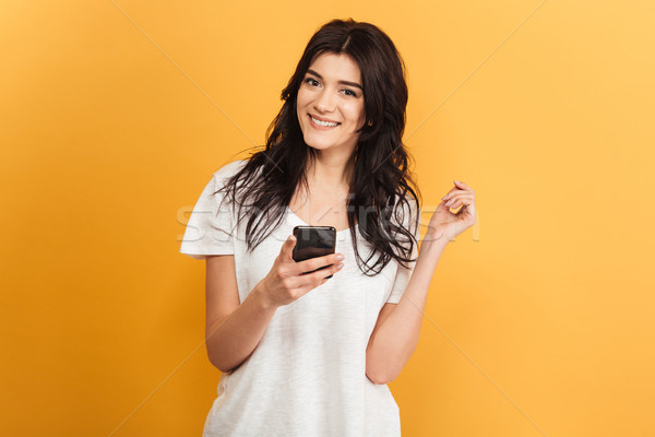 Cute young pretty woman looking camera chatting by mobile phone. Stock photo © deandrobot