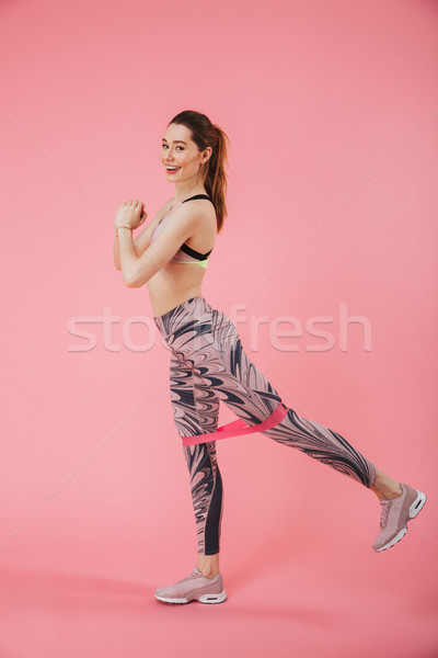 Vertical side view image of happy sportswoman doing fitness exrcise Stock photo © deandrobot