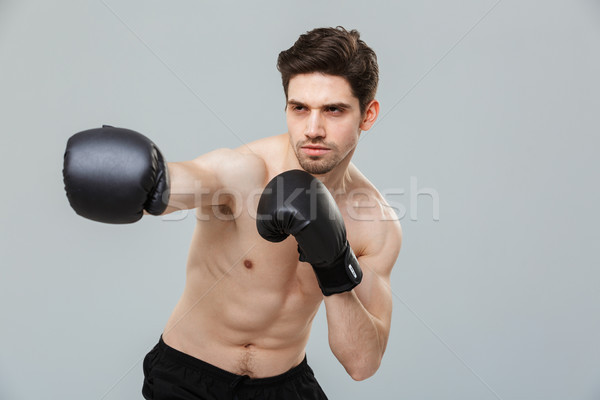 Portrait of a concentrated young sportsman exercising Stock photo © deandrobot