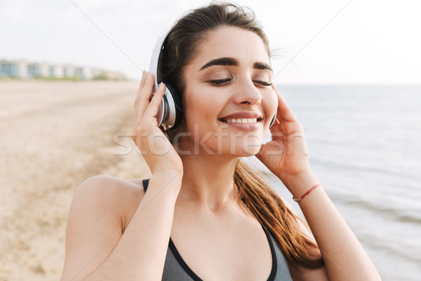 Close up of a pretty young sportswoman in headphones Stock photo © deandrobot