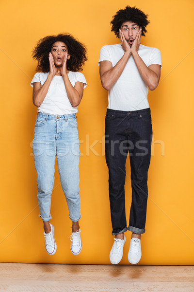 Full length portrait of a surprised young afro american couple Stock photo © deandrobot
