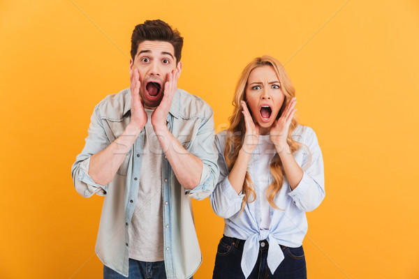 Image of shocked people man and woman in basic clothing expressi Stock photo © deandrobot