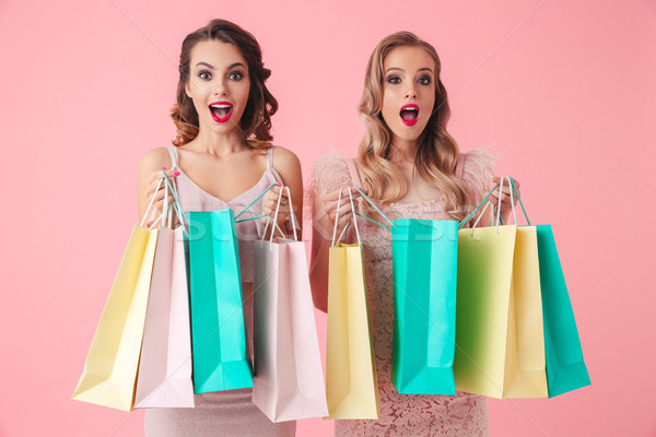 Two surprised happy women in dresses opening packages Stock photo © deandrobot