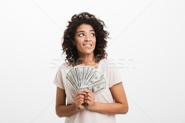 Adorable american woman with curly brown hair holding fan of mon Stock photo © deandrobot