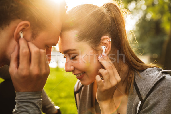 Image of happy young people man and woman 20s in tracksuits, lis Stock photo © deandrobot