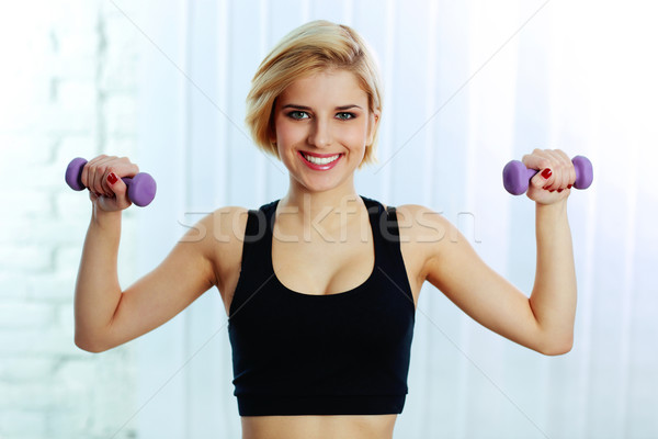 Portrait of a young fit woman doing workout with dumbbells Stock photo © deandrobot