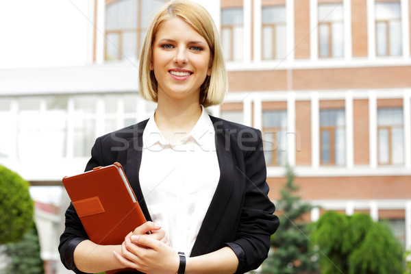 Portrait of a young smiling woman holding tablet computer outdoors Stock photo © deandrobot