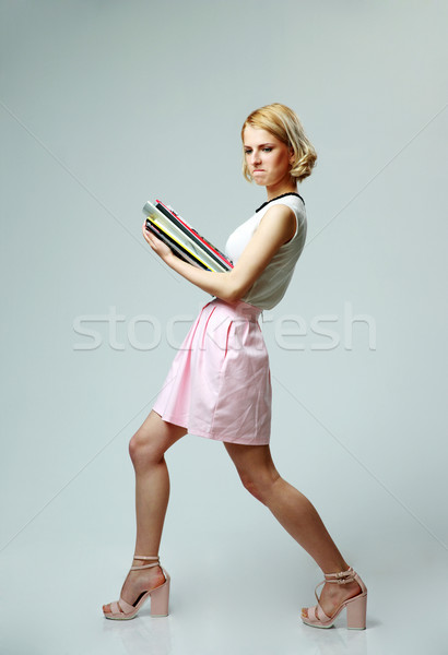 Studio shot of a young woman with notebooks on gray background Stock photo © deandrobot