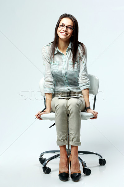 Young smiling businesswoman sitting on office chair on gray background Stock photo © deandrobot