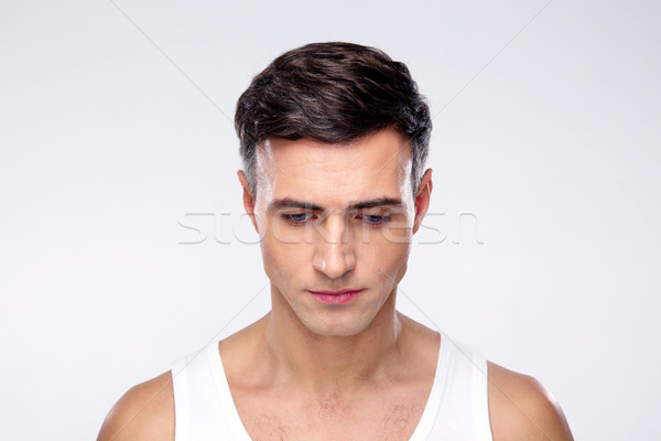 Portrait of a young pensive man over gray background Stock photo © deandrobot