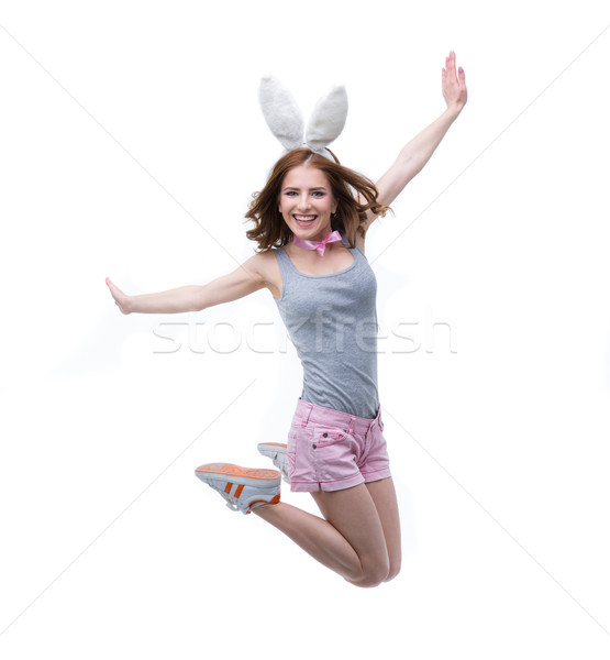 Happy woman in rabbit ears jumping over white background Stock photo © deandrobot
