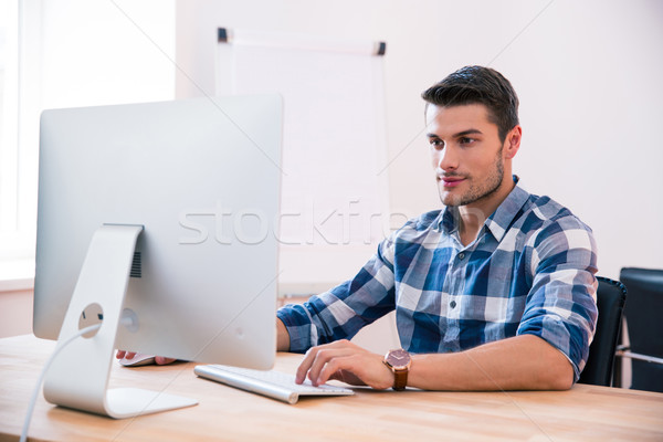 Handsome businessman using PC at the table Stock photo © deandrobot