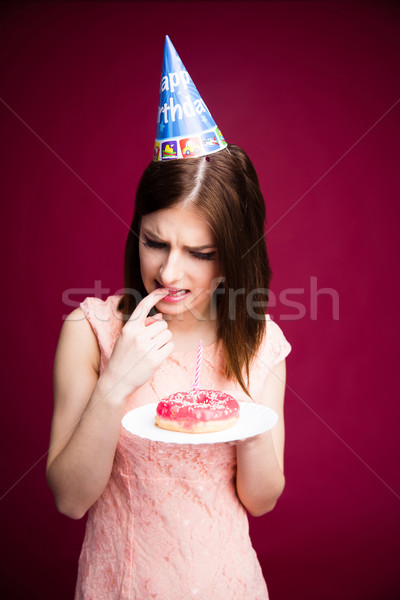 Stock photo: Young woman holding donut with candle