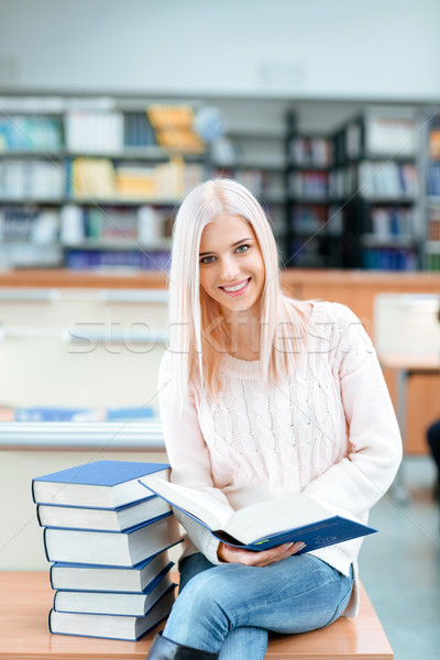 Girl sitting on the desk with pile of books Stock photo © deandrobot