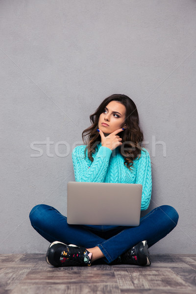 Pensive woman sitting on the floor with laptop Stock photo © deandrobot