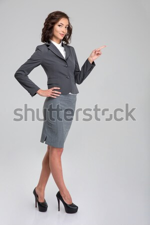Young pretty woman in formalwear pointing away on copyspace Stock photo © deandrobot