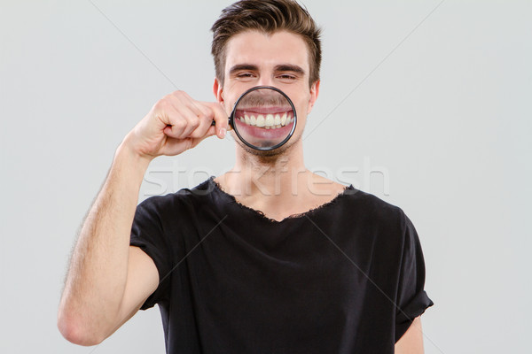 Young guy having fun with magnifying glass Stock photo © deandrobot