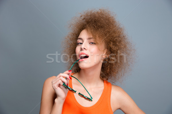 Playful confident curly female posing with sunglasses Stock photo © deandrobot