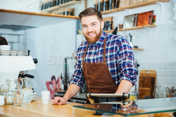 Cheerful handsome young barista with beard working in coffee shop Stock photo © deandrobot