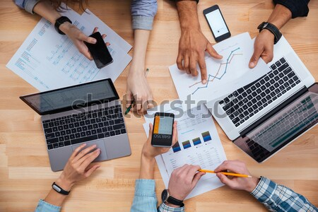 Business people using mobile phones and laptops for making  report Stock photo © deandrobot