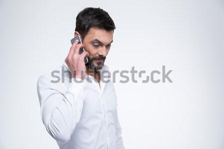 Jóképű üzletember beszél telefon izolált fehér Stock fotó © deandrobot