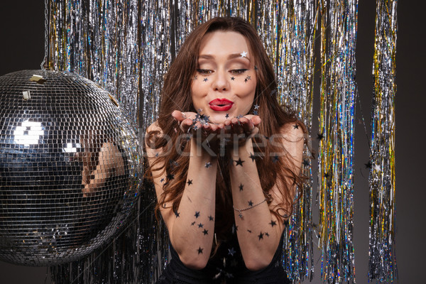 Cute lovely young woman blowing on small sparkling stars Stock photo © deandrobot