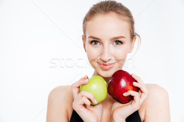 Closeup of smiling pretty sportswoman with green and red apples  Stock photo © deandrobot