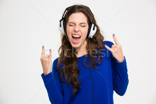 Excited woman in headphones listening to music and gesturing rock  Stock photo © deandrobot
