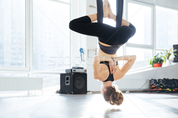 Attractive young woman doing antigravity yoga using hammock  Stock photo © deandrobot