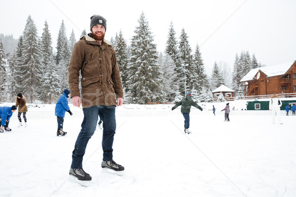 Happy man ice skating outdoors Stock photo © deandrobot