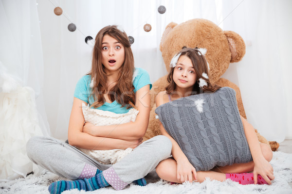 Two amazed lovely sisters sitting and hugging pillow Stock photo © deandrobot