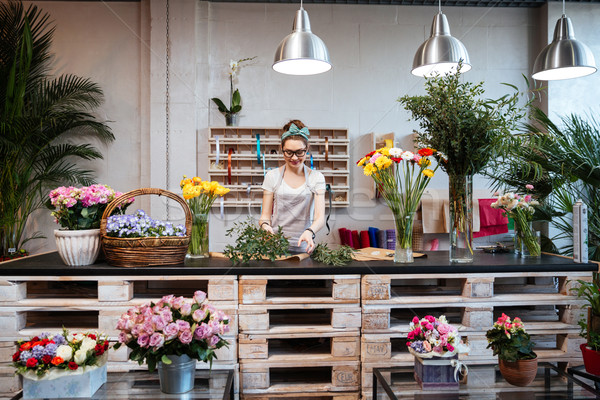 Smiling woman florist standing and working in flower shop Stock photo © deandrobot