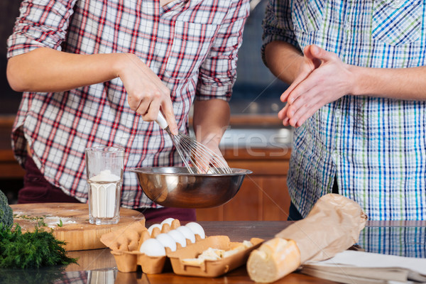 Young couple beating eggs and cooking omelette on the kitchen Stock photo © deandrobot