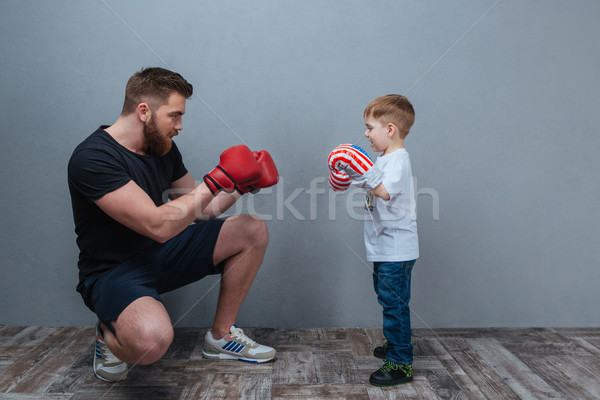 Dad and little son playing in boxing gloves together Stock photo © deandrobot