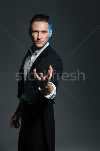 Mysterious magician holding something on palm  Stock photo © deandrobot